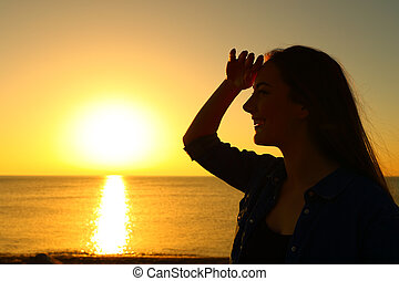 Silhouette of a woman scouting at sunrise on the beach