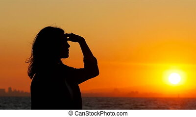Silhouette of a woman scouting at sunset