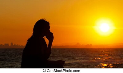 Silhouette of a woman talking on phone at sunset