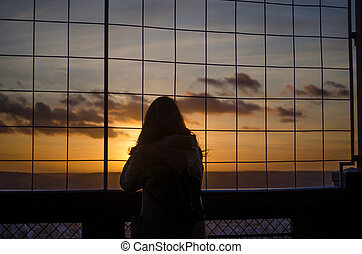 Silhouette of a woman watching the sunset