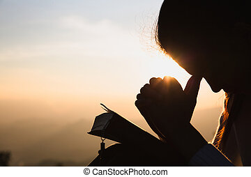 Silhouette of a woman with hands raised in the sunset concept for religion, worship, prayer and praise, Religious concepts