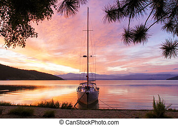 Silhouette of a yacht with a lowered ladder on Lake Baikal at dawn.