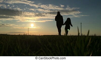 Silhouette of a young couple holding hands running in slow...