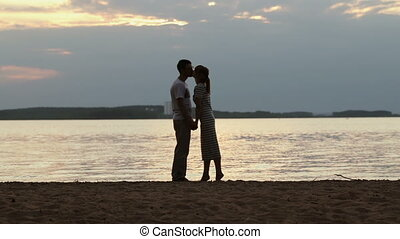 Silhouette of a young couple in love at sunset. Girl stood on tiptoe and gently kisses the guy on the shore of the lake