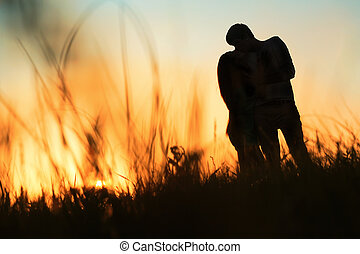 silhouette of a young couple kissing at sunset