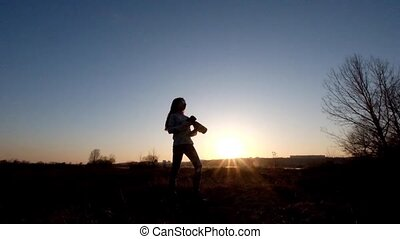 Silhouette of a young girl-photographer at sunset