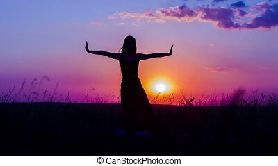 Silhouette of a Young Girl Practicing Yoga At Nature During Sunset