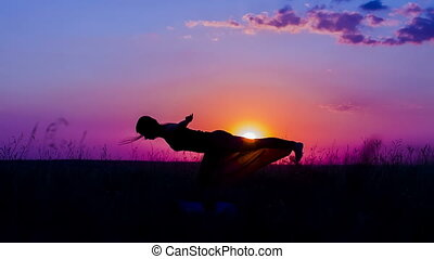 Silhouette of a Young Girl Practicing Yoga Asanas At  Sunset