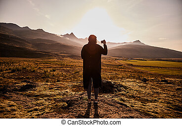 Silhouette of a young girl who takes pictures on the phone Icelandic landscape. Sunset in Iceland.