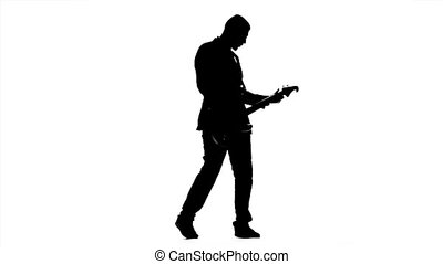 Silhouette of a young man playing the guitar. Slow motion