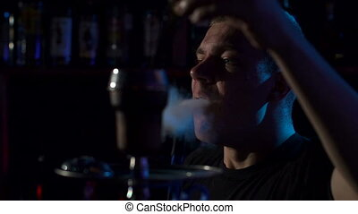 Silhouette of a young man Smoking a hookah in the dark, slow motion. Close-up.