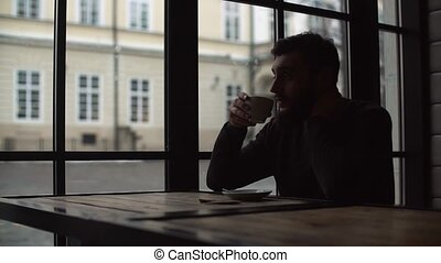 Silhouette of a young man who drinking coffee in a cozy cafe.