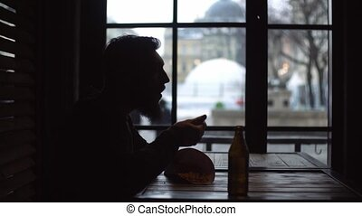 Silhouette of a young man who is drinking beer and eating snacks at the bar by the window.