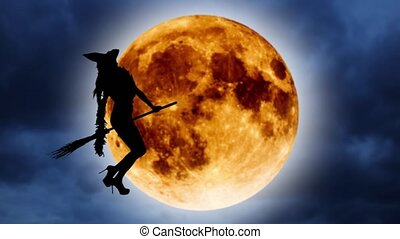 Silhouette of a young witch flying on a broomstick against the background of the orange moon. Halloween