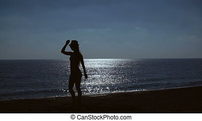 silhouette of a young woman dancing on beach on sea background