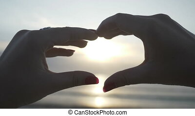 Silhouette of a young woman hands wearing rings making a heart shape with sunset inside on the beach in slow motion