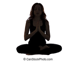 Silhouette of a young woman sitting and meditating