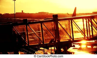 Silhouette of a young woman walking in a glass jet bridge....