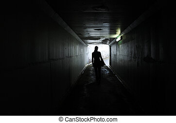 Silhouette of a young woman walks alone in a dark tunnel