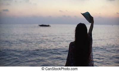 silhouette of a young woman with long hair waving hat against sea at sunset