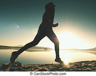 Silhouette of active athlete runner running on sunrise shore. Morning healthy lifestyle exercise