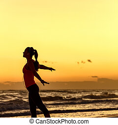 Silhouette of active woman in sportswear on beach rejoicing