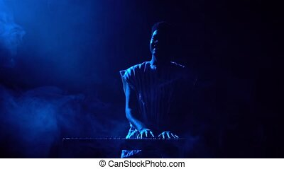 Silhouette of african american man playing piano synthesizer on stage in dark smoky studio. Black musician with white ethnic pattern on his face performs against background of blue lights