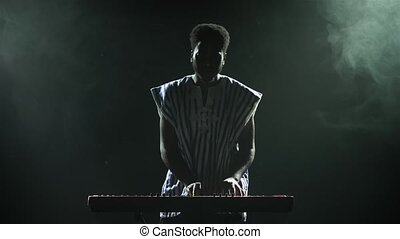 Silhouette of african american man playing piano synthesizer on stage in dark smoky studio. Black musician with a white ethnic pattern on his face performs against the background of lights
