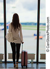 Silhouette of airline passenger in an airport lounge waiting for flight aircraft