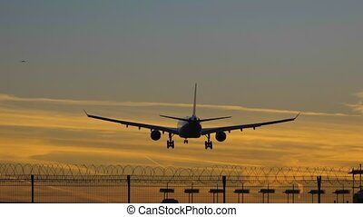 silhouette of airplane landing at the airport