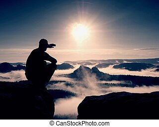 Silhouette of alone hiker in black and cap sit on cliff. ...