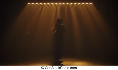 Silhouette of an attractive woman in a pantsuit and hat ...