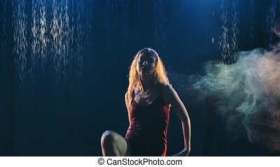 Silhouette of an attractive woman passionately dancing in the rain on a smoky background. Slow motion. Close up