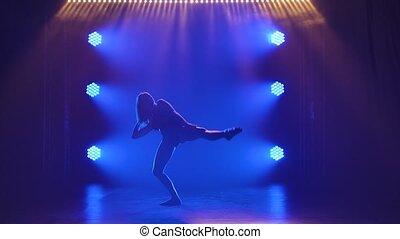 Silhouette of an attractive woman who is dancing a beautiful...