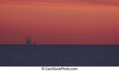 silhouette of an oil drilling at sunset closeup footage