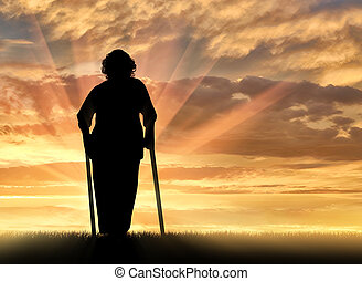 Silhouette of an old woman on crutches outdoors