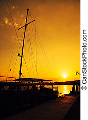 Silhouette of an one-masted touring boat at sunset
