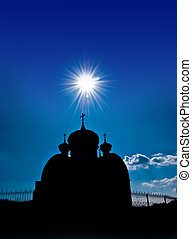 Silhouette of an orthodox temple against the sky and the sun