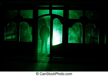 Silhouette of an unknown shadow figure on a door through a closed glass door. The silhouette of a human in front of a window at night. Scary scene halloween concept of blurred silhouette