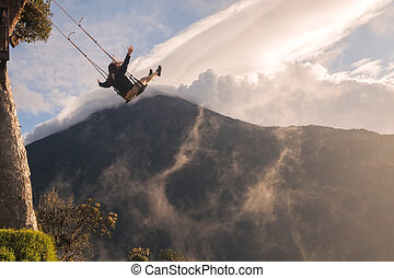 Silhouette Of An Young Happy Woman On A Swing, Swinging Over The Andes Mountains, Tungurahua Volcano In The Background, Tree House, Ecuador