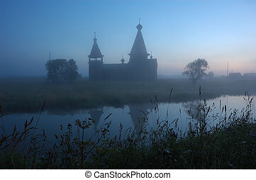 Silhouette of ancient wooden church at sunrise