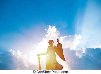 silhouette of angel statue sculpture with sunlight shining behind white cloud with blue sky background