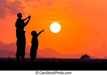 silhouette of asian little boy point to the sun at sunset backgrond