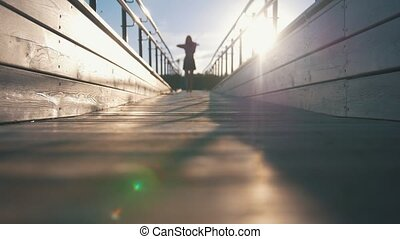 Silhouette of attractive woman playing violin walking on a footbridge at sunset