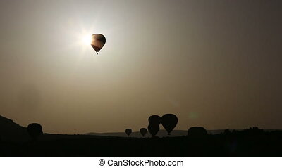 Silhouette of balloon over hill at sunset
