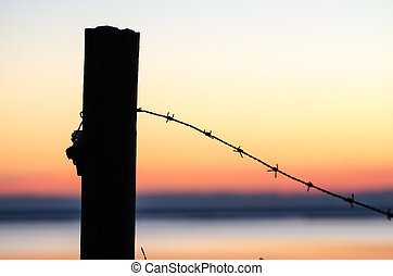 Silhouette of barb wire at a post