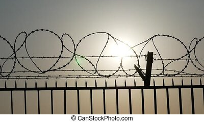 Silhouette of barbed and razor wire on the fence -...