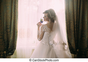 Silhouette of beautiful bride in traditional white wedding dress, stood by window.