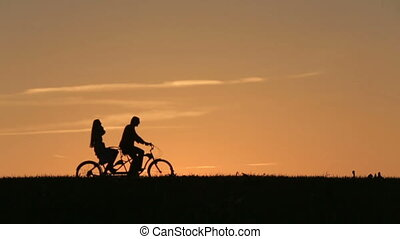 Silhouette of Beautiful Couple Riding The Tandem Bicycle...
