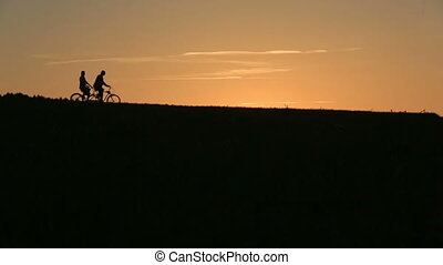 Silhouette of  Beautiful Couple Riding The Tandem Bicycles While Sunset. Summer Nature Background with Beautiful Clouds in the Sky Close Up